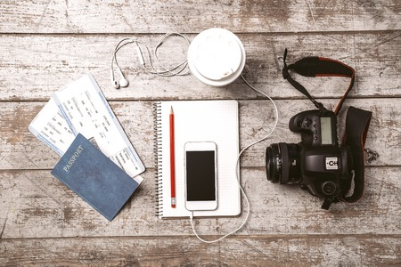 foto carnet: Vista superior foto de teléfono blanco móvil, cámara profesional, cuaderno, pasaporte, billetes, lápiz, taza y auriculares. Los objetos son de la luz piso de madera de color