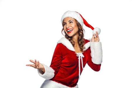 young girl nude: Christmas portrait of beautiful mixed-race santa girl. Young sexy brunette woman wearing santa claus clothes. Snow Maiden cheerfully smiling on white background Stock Photo