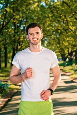 nice guy: Photo of handsome nice guy outdoors at morning. Young man looking at camera and smiling while running in park