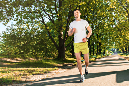 nice guy: Photo of handsome nice guy outdoors at morning. Young man smiling while running in park