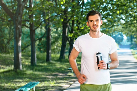nice guy: Photo of handsome nice guy outdoors at morning. Young man looking at camera and holding sport drink shaker while running in park