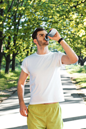 nice guy: Photo of handsome nice guy outdoors at morning. Young man drinking water while run in park Stock Photo