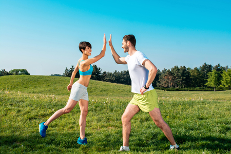 nice guy: Photo of handsome nice guy and sporty slim girl outdoors at morning. Young man and woman doing high five and cheerfully smiling while running in park
