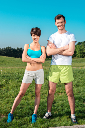 nice guy: Photo of handsome nice guy and sporty slim girl outdoors at morning. Young man and woman looking at camera and cheerfully smiling while run in park