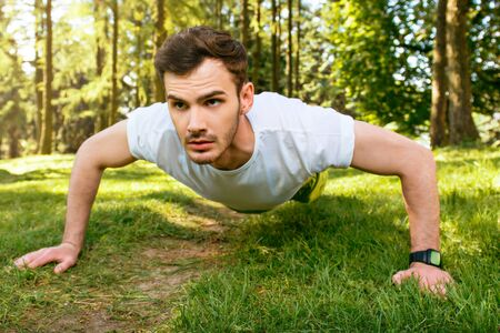 nice guy: Photo of handsome nice guy outdoors at morning. Young man doing push up exercises while training in park Stock Photo