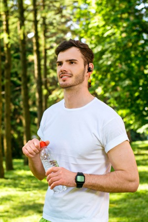 nice guy: Photo of handsome nice guy outdoors at morning. Young man with headphones holding bottle of water while running in park Stock Photo