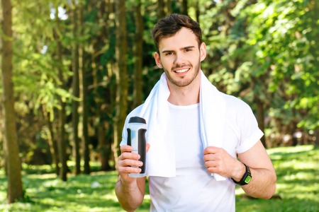 nice guy: Photo of handsome nice guy outdoors at morning. Young man with towel on shoulders looking at camera, smiling and holding sport drink shaker while running in park Stock Photo
