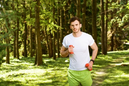 nice guy: Photo of handsome nice guy outdoors at morning. Young man running with dumbbells in park Stock Photo