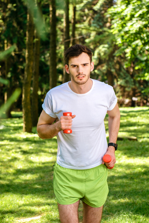 nice guy: Photo of handsome nice guy outdoors at morning. Young man looking at camera and running with dumbbells in park