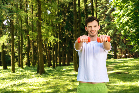 nice guy: Photo of handsome nice guy outdoors at morning. Young man smiling, looking at camera and doing sport exercises with dumbbells while training in park