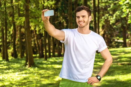nice guy: Photo of handsome nice guy outdoors at morning. Young man smiling and making selfie photo on mobile phone while running in park Stock Photo