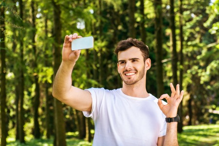 nice guy: Photo of handsome nice guy outdoors at morning. Young man smiling, showing ok sign and making selfie photo on mobile phone while running in park