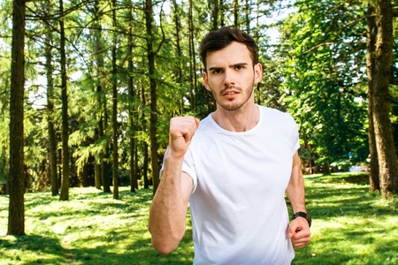 nice guy: Photo of handsome nice guy outdoors at morning. Young man training and running in park Stock Photo
