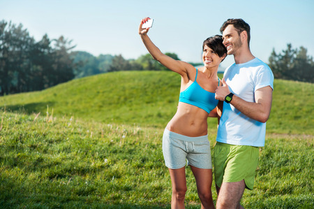 nice guy: Photo of handsome nice guy and sporty slim girl outdoors at morning. Young man and woman smiling and making selfie photo on mobile phone while run in park Stock Photo
