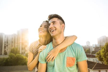 소녀와 소년 야외에서 옥상에 앉아입니다. 그들은 즐겁게 웃고 좋은 날씨를 즐기고 있습니다. 멋진 도시의 파노라마