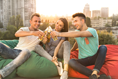 Group of friends enjoying drinks outdoors at roof while having party. They cheerfully smiling and sitting on bag chairs. Nice city panorama Stock Photo