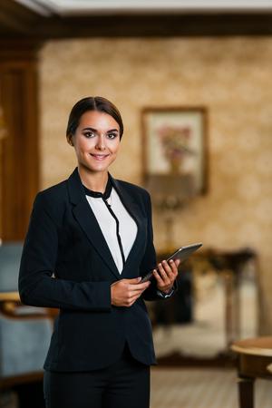 Giovane donna d'affari che indossa abito, in piedi in una bella camera d'albergo, utilizzando il computer tablet e guardando la fotocamera Archivio Fotografico - 47354615
