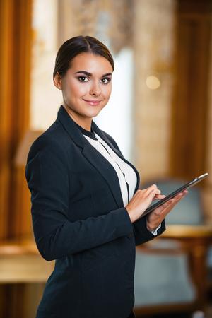 비싼 호텔에서 비즈니스 여자의 사진입니다. 태블릿 컴퓨터를 사용 하 고 카메라를 찾고 좋은 호텔 방에 서있는 양복을 입고 젊은 비즈니스 여자 스톡 콘텐츠