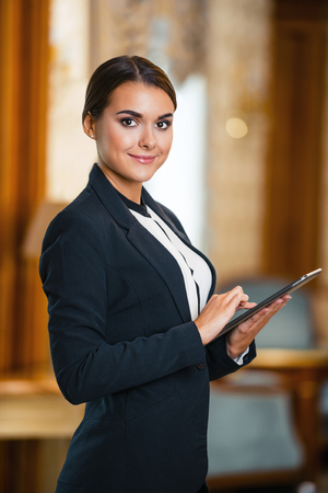Photo of business woman in expensive hotel. Young business woman wearing suit, standing in nice hotel room, using tablet computer and looking at camera