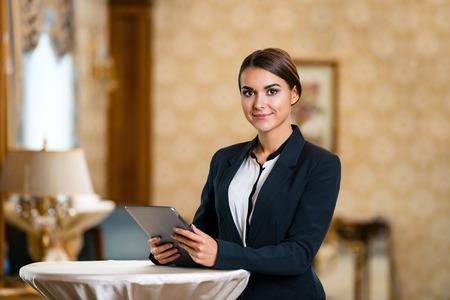 태블릿 컴퓨터를 사용 하 고 카메라를 찾고 좋은 호텔 방에 서있는 양복을 입고 젊은 비즈니스 여자