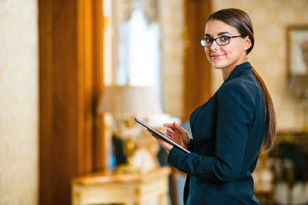 Young business woman wearing suit and glasses, standing in nice hotel room, using tablet computer and looking at camera