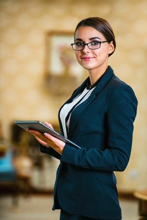 양복과 안경, 좋은 호텔 방에 서 태블릿 컴퓨터를 사용하고 카메라를 찾고 입고 젊은 비즈니스 여자