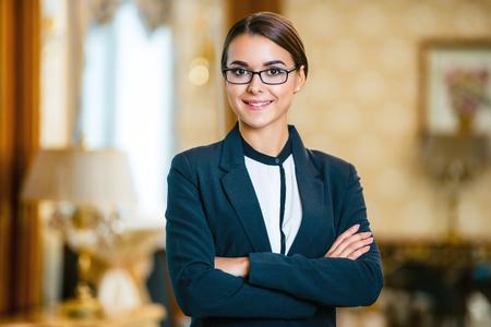 Giovane donna d'affari che indossa tuta e occhiali, in piedi nella bella camera d'albergo e guardando la fotocamera Archivio Fotografico - 47354680