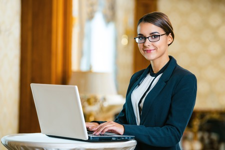 Young business woman wearing suit and glasses, standing in nice hotel room, using laptop and looking at camera