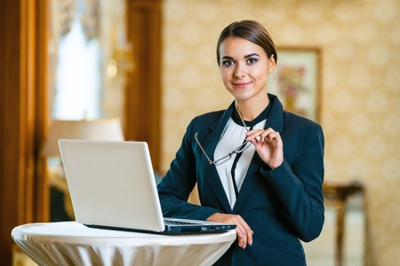 Young business woman wearing suit, standing in nice hotel room, using laptop and looking at camera