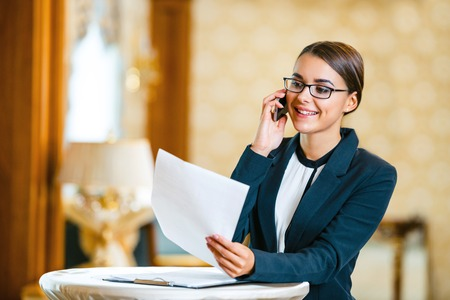 Young business woman wearing suit and glasses, standing in nice hotel room, talking by phone and looking at documents