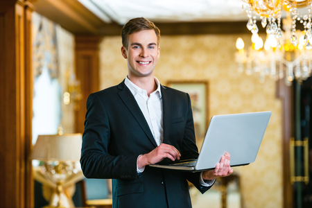Young smiling businessman wearing suit, standing in nice hotel room, using laptop and looking at camera