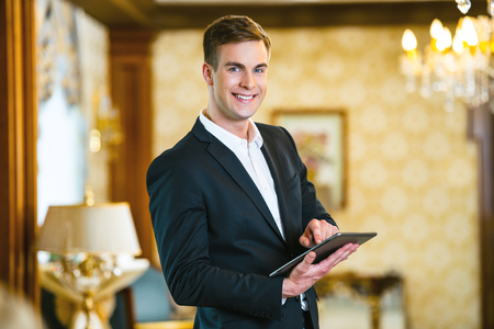 Young smiling businessman wearing suit, standing in nice hotel room, using tablet computer and looking at camera