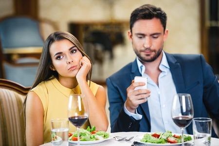 若い女性は彼女のボーイ フレンドの携帯電話を使用しながら退屈と孤独をします。