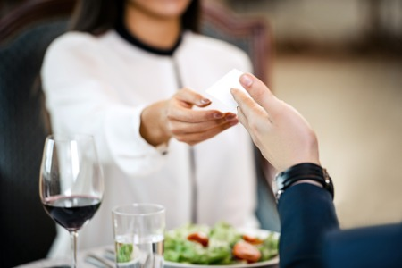 room accents: Young business woman having dinner with businessman. Man giving visit card to business woman