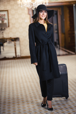 nice looking: Young woman wearing hat and coat, standing in nice hotel room with her suitcase and looking at camera