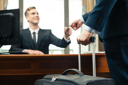 受付に自分のクレジット カードを与えるスーツケースを持つ顧客