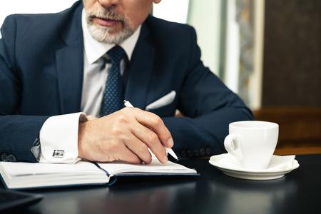 liderazgo empresarial: Cerrar una foto del hombre de negocios en la oficina usando traje caro y clásico, tomando notas y tomando un café Foto de archivo