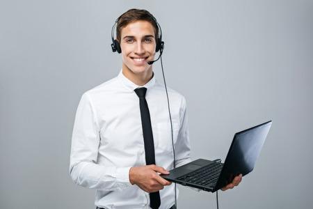 computer centre: Retrato de guapo joven de sexo masculino operador de centro de llamadas de pie sobre fondo gris que desgasta la camisa, auriculares y lazo, sosteniendo el ordenador port�til y mirando a la c�mara Foto de archivo