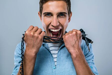 gray haired: Portrait of handsome stylish young man standing on grey background. Angry man with wires on hands trying to bite it