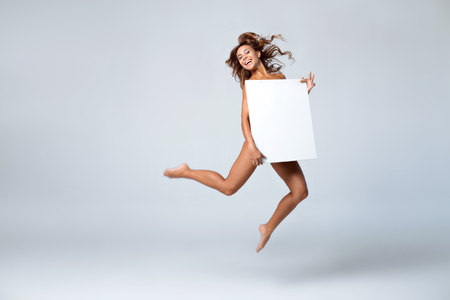 people smile: Young brunette woman hiding behind blank white square paper and jumping