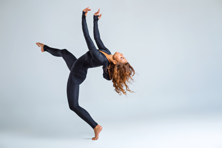 close fitting: Young brunette woman wearing close-fitting black suit and making dance elements Stock Photo