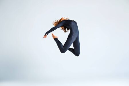 close fitting: Young brunette woman wearing close-fitting black suit, jumping and making dance elements Stock Photo