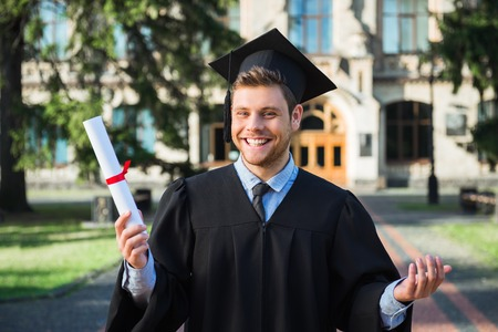 Young male student dressed in black graduation gown. Campus as a background. Boy cheerfully smiling, holding diploma and looking at camera