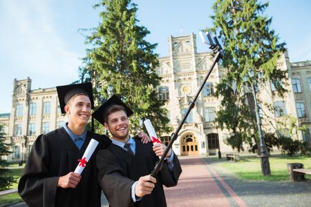 toga y birrete: Estudiantes varones jóvenes vestidos con traje de graduación negro. Campus como fondo. Niños sonriendo con alegría, la celebración de los diplomas y hace la foto con el palillo selfie