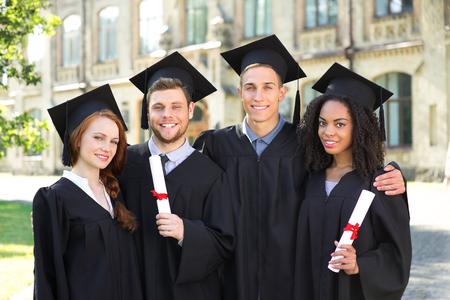 niño y niña: Jóvenes estudiantes vestidos con traje de graduación negro. Campus como fondo. Los niños y las niñas sonrientes, abrazos, la celebración de los diplomas y mirando a cámara