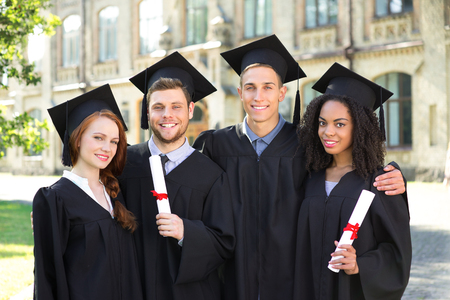girl in a hat: Young students dressed in black graduation gown. Campus as a background. Boys and girls smiling, hugging, holding diplomas and looking at camera Stock Photo