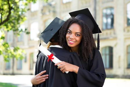 graduacion: Las estudiantes j�venes vestidos con traje de graduaci�n negro. Campus como fondo. Muchachas que sostienen los diplomas y abrazan unos a otros Foto de archivo