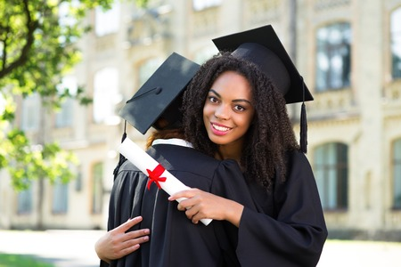 graduation: Young female students dressed in black graduation gown. Campus as a background. Girls holding diplomas and embracing one another Stock Photo