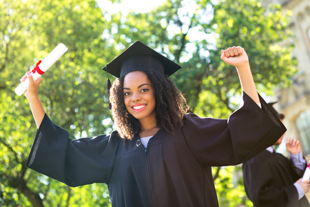 Young Afro American female student dressed in black graduation gown. Campus as a background. Girl cheerfully smiling with arms up, holding diploma and looking at camera Stockfoto