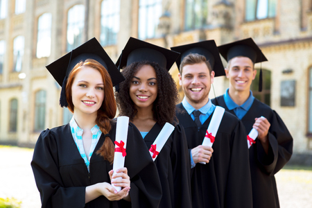 Young students dressed in black graduation gown. Campus as a background. Students standing in row, smiling, holding diplomas and looking at camera Stock Photo